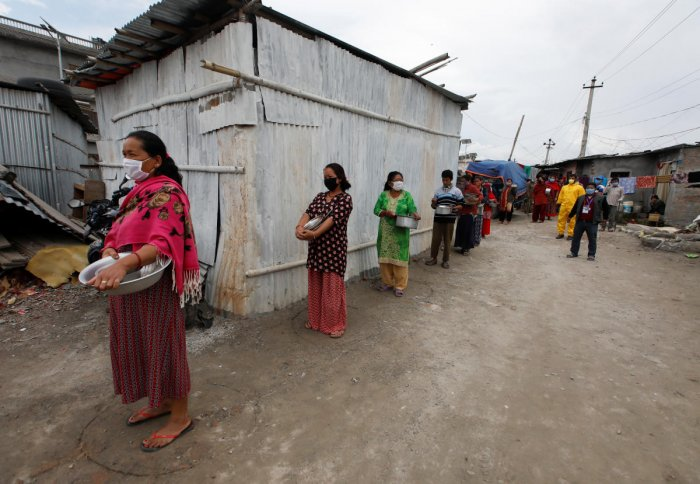 People maintain social distance as they wait for food distributed by the volunteers during the thirty-six days of the lockdown imposed by the government amid concerns about the spread of coronavirus disease (COVID-19) outbreak, at a slum in Kathmandu, Nepal April 28, 2020. Reuters Photo