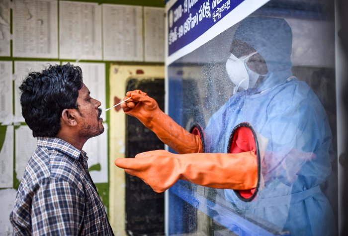 Vijayawada: A healthcare worker collects a swab sample of a man for COVID-19 test from the swab collection booth (PTI photo)