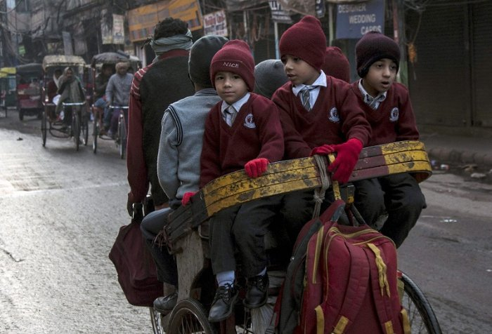 School children travel to school in a cycle rickshaw on a cold winter morning in the old quarters of Delhi. (PTI Photo