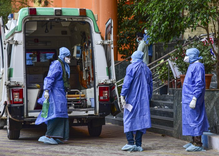 Medical workers attend to a suspected coronavirus patient (L), who travelled from Dubai, as he is shifted to the isolation ward of Gandhi Hospital. (PTI Photo)