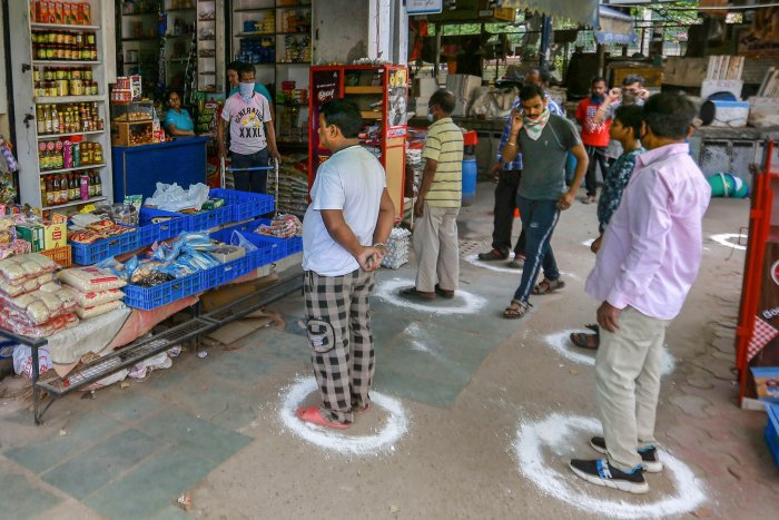 People maintain social distance as they wait outside a grocery shop during a 21-day nationwide lockdown in the wake of coronavirus pandemic, at CR Park, in New Delhi. (Credit: PTI)