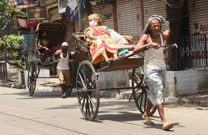 Passengers wearing face masks are seen on hand-pulled rickshaws during the ongoing nationwide lockdown in the wake of coronavirus pandemic, in Kolkata. (Credit: PTI Photo)