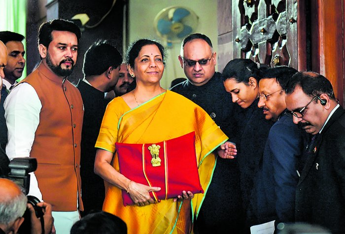 Union Finance Minister Nirmala Sitharaman, flanked by her deputy Anurag Thakur (to her right) and a team of officials, shows a folder containing the Union Budget documents as she poses for lensmen on her arrival at Parliament in New Delhi, Saturday, Feb. 1, 2020. (PTI Photo/Manvender Vashist)