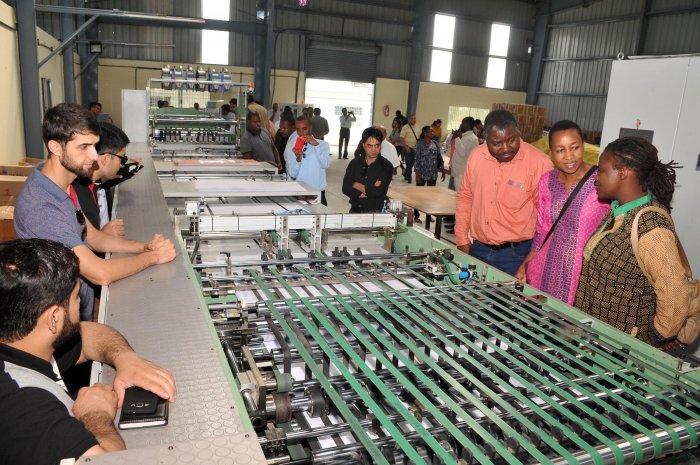 Foreign delegates take look on machinery at N J Stationary, in Mysuru