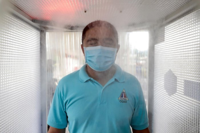 A man wearing a face mask uses a disinfection booth that mists ethyl alcohol to contain the spread of coronavirus disease (COVID-19) in Quezon City, Metro Manila, Philippines. (Reuters photo)