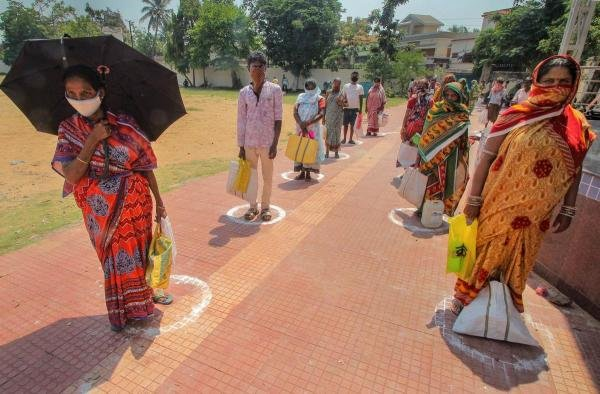 Beneficiaries stand in a queue, maintaining social distancing, to collect ration at state government PDS ration centre during the nationwide lockdown amid coronavirus outbreak, in Bhubaneswar. (PTI Photo)