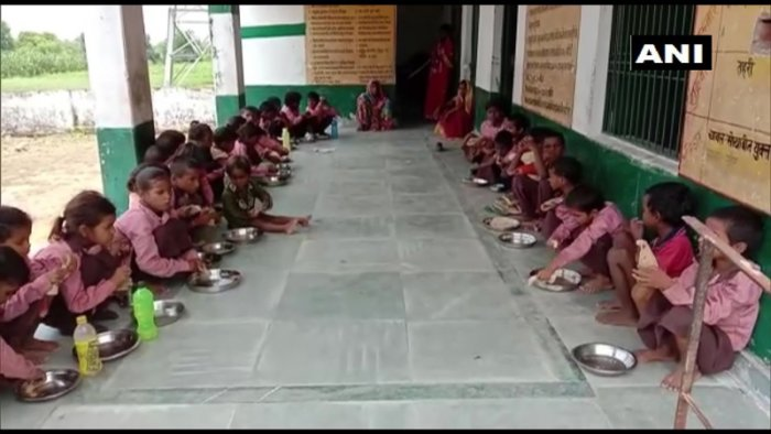 Students being served salt and roti in the Siyur Primary School. (Photo credit: ANI/twitter)