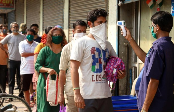 A worker screens customers outside a grocery store during a 21-day nationwide lockdown in the wake of coronavirus pandemic, in Thane, Wednesday, March 25, 2020. (PTI Photo)