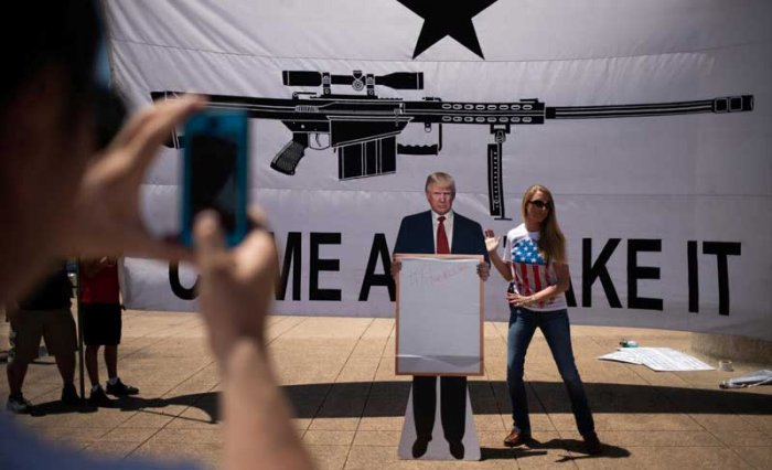Bill Wang photographs his wife Brooke Wang as she sets a cardboard cutout of U.S. President Donald Trump in front of a banner during an open carry firearm rally on the sidelines of the annual National Rifle Association (NRA) meeting in Dallas, Texas, U.S., May 5, 2018. REUTERS
