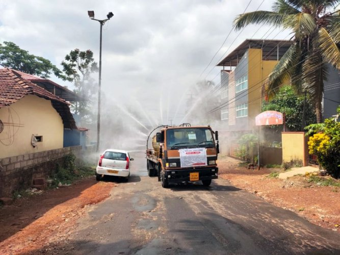 Disinfectant being sprayed in Shakthinagara, Mangaluru, on Tuesday after a mother and son tested positive. Credit: DH Photo
