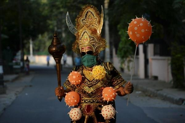 A man dressed as 'Yamraj', the Hindu mythical angel of death, campaigns to raise awareness on the importance to stay home and maintain social distancing during an event organised by Delhi police as India continues to remain under a nationwide lockdown as a preventive measure against the spread of the COVID-19 coronavirus, in New Delhi on April 28, 2020. (AFP Photo by Sajjad Hussain)