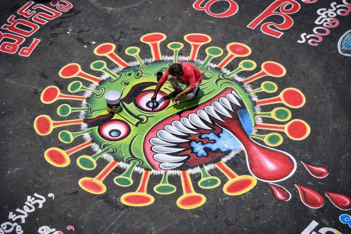 An artist paints a graffiti on a road depicting the coronavirus as an attempt to raise awareness about the importance of staying at home. PTI