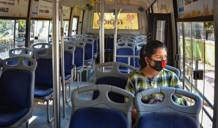 A passenger wears a protective mask to mitigate the coronavirus pandemic as she sits inside an empty bus, in Guwahati, Thursday, March 19, 2020. (PTI Photo)