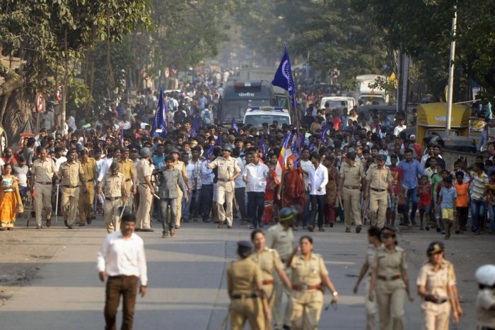 Policemen accompany the Dalits protestors as they stage a protest against the violence in Bhima Koregaon area of Pune, in Mumbai on Tuesday. Photo/PTI
