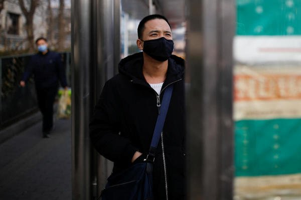 A man wearing a face mask looks at a board at a bus stop, as the country is hit by an outbreak of the new coronavirus, in Beijing, China January 27, 2020. (Reuters Photo)