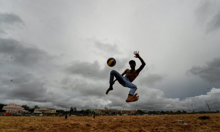 A boy plays football on a cloudy day at Marina beach in Chennai, on Friday. The Indian Meteorological Department has issued a warning predicting heavy to very heavy rainfall in the region with a red alert announced for three districts of Kerala – Idukki, Palakkad and Thrissur for October 7. PTI