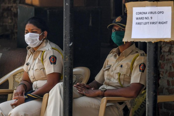 Police personnel wearing facemasks amid concerns over the spread of the COVID-19 novel coronavirus sit at the entrance of a hospital with a special ward for the virus in Mumbai on March 17, 2020. Credit: AFP Photo