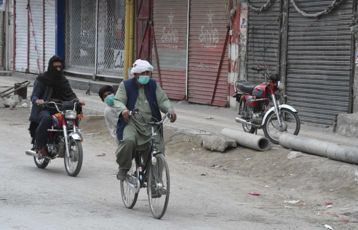 Commuters wearing facemasks as a preventive measure against the COVID-19 coronavirus make their way past closed shops in Quetta on March 22, 2020. Credit: AFP Photo