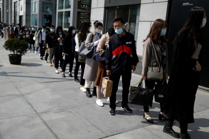 People wearing face masks, following the coronavirus disease (COVID-19) outbreak, make a line to enter an office building in Beijing. Reuters
