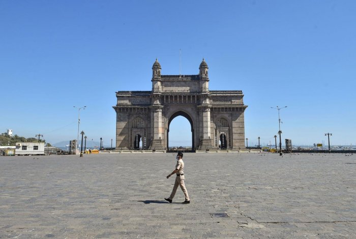 A policeman wearing protective mask in the wake of coronavirus pandemic, walks past a deserted Gateway of India. PTI