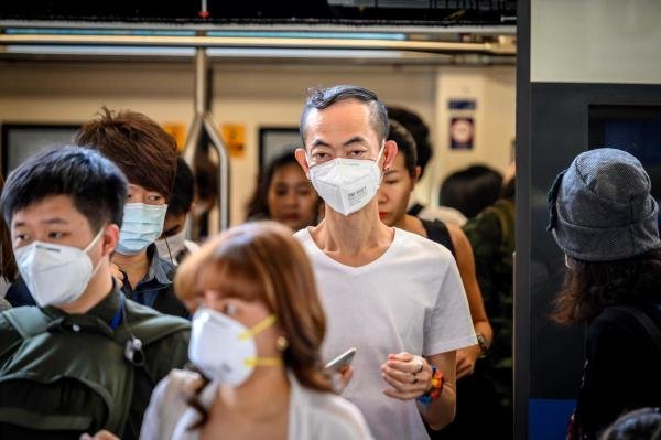 People with face masks ride a BTS Sky train in Bangkok on January 27, 2020. (AFP Photo)