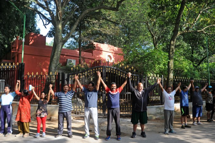 People form a human chain at Cubbon Park in protest against the proposed construction of a 7-story building in the park area in Bengaluru on Sunday. | DH Photo: Pushkar V