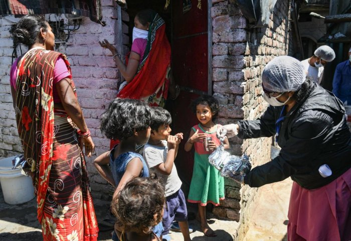 Members of an NGO give away food items to children at a slum, during ongoing COVID-19 lockdown in Dehradun, Tuesday, April 21, 2020. (PTI Photo)