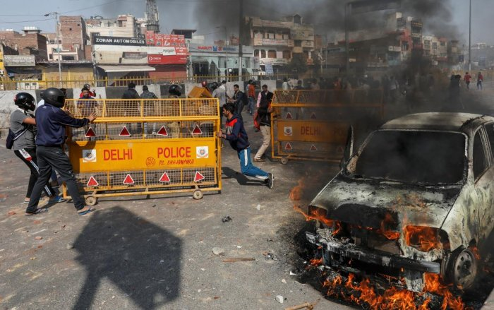 People supporting a new citizenship law push police barricades during a clash with those opposing the law in New Delhi India, February 24, 2020. REUTERS/Danish Siddiqui