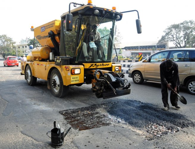 BBMP employees seen busy with filling potholes by using new pothole filling machine 'Python 5000' an product of American Road Technology & Solutions Private limited at busy Race Cource road in Bangalore on Friday afternoon. Photo by Satish Badiger