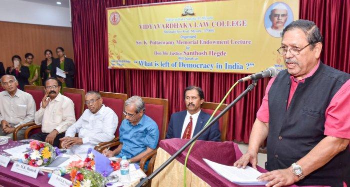 Former Lokayukta Justice Santhosh Hegde speaking at the Late Sir K Puttaswamy Memorial Endowment lecture on 'What is left of Democracy in India?', organised at Vidyavardhaka Law College in Mysuru on Friday. Vidyavardha Sangha Secretary P Vishwanath, Presi