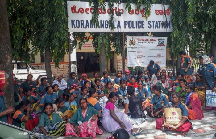 Pourakarmikas stage a protest in front of the Koramangala police station on Monday.
