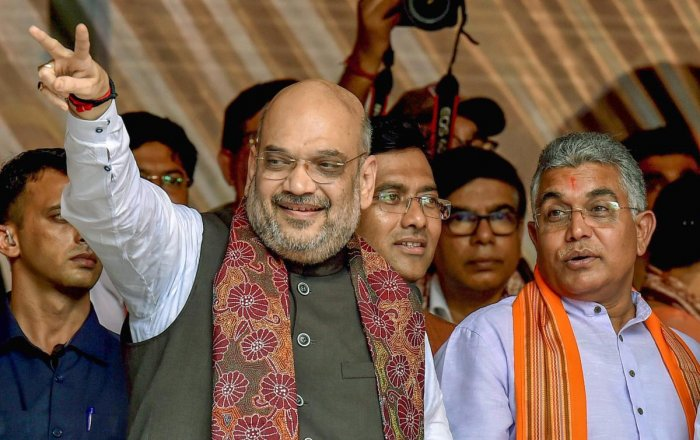 BJP president Amit Shah flashes the victory sign as West Bengal BJP president Dilip Ghosh looks on, during a public rally in Kolkata im 2018. PTI