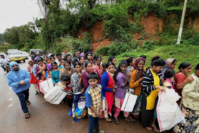 Kodagu: Flood-affected people queue to receive relief material near a relief camp in Kadagu, Karnataka on Tuesday, Aug 21, 2018. (PTI Photo)