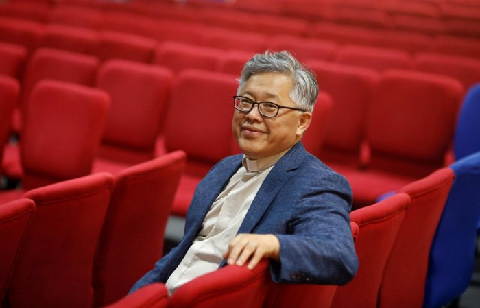 """The head pastor of the Zion church in Beijing Jin Mingri poses for picures in the congregation hall of the unofficial Protestant """"house"""" church in Beijing, China, on August 28, 2018. Reuters"""