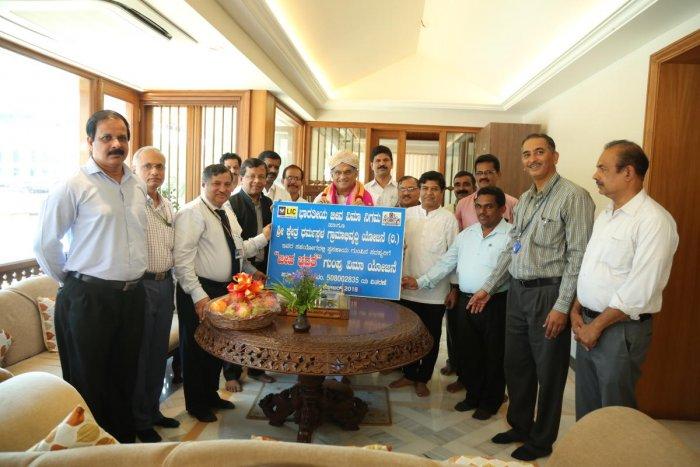 LIC of India Zonal Manager T C Susheel Kumar hands over the master policy of Jeeva Bima Bhadrathe scheme to Dharmasthala Dharmadhi D Veerendra Heggade.