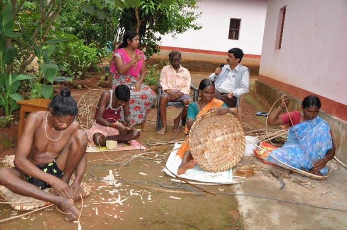 Members of Koraga community engaged in weaving baskets.