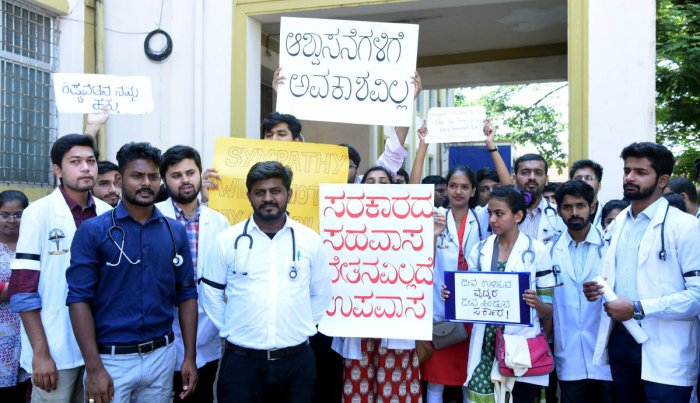 Medical interns and postgraduate doctors serving at Government Wenlock Hospital, Regional Advanced Paediatric Care Centre and Lady Goschen Hospital, stage a protest in front of Wenlock Hospital, in Mangaluru on Monday.