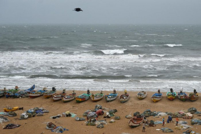 Fishing boats are seen on shore as waves pound the coast during rainy weather at Pattinapakkam beach in Chennai on Wednesday. AFP