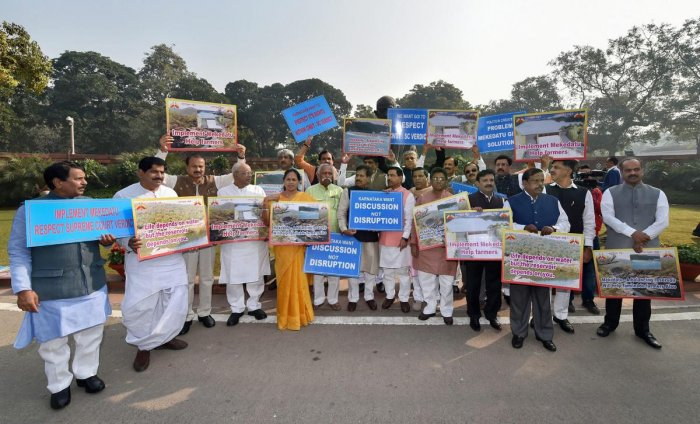 Karnataka MPs hold placards during a protest over the Mekedatu dam project in front of the Gandhi statue during the Winter Session of Parliament, in New Delhi on Thursday.