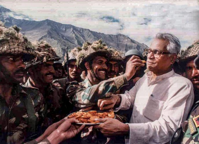 In this undated file photo, then defence minister George Fernandes shares snacks with the Army personnel during a visit to Ganasok in the Batalik Sector, J & K. (PTI file photo)