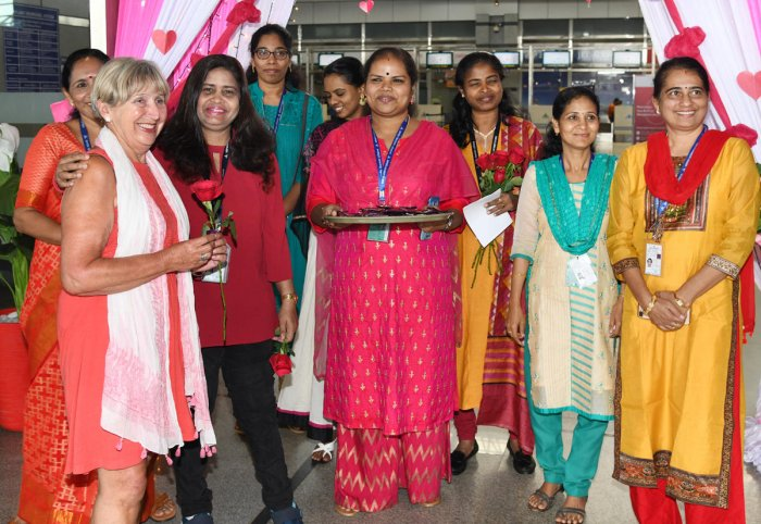 A woman passenger is greeted with a rose at Mangaluru International Airport in Bajpe, Mangaluru, on account of International Women's Day, on Friday.