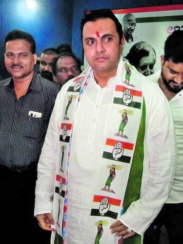 Congress-JD(S) coalition candidate for Udupi-Chikmagalur constituency Pramod Madhwaraj appears wearing a shawl with symbols of both the parties in Udupi on Friday.