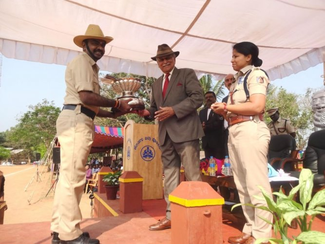 Former Air Marshal K C Cariappa presents the Field Marshal K M Cariappa Trophy to Siddapur police station constable K A Siddartha during the state Police Flag Day programme at the district police grounds in Madikeri on Tuesday.