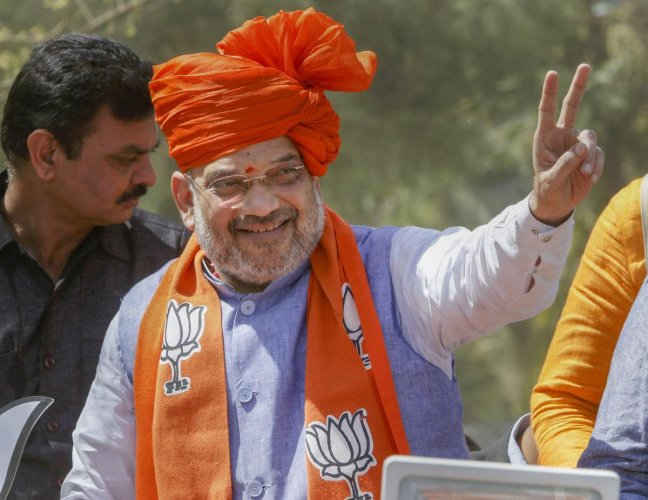 BJP President Amit Shah flashes victory sign during an election campaign roadshow, ahead of the general elections-2019, in Ahmedabad, April 6, 2019. (PTI Photo)