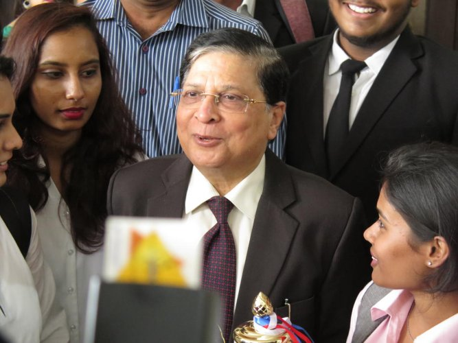Former Chief Justice of India, Dipak Misra, stands with students at the KLE Law College in Bengaluru on Monday, April 8, 2019.