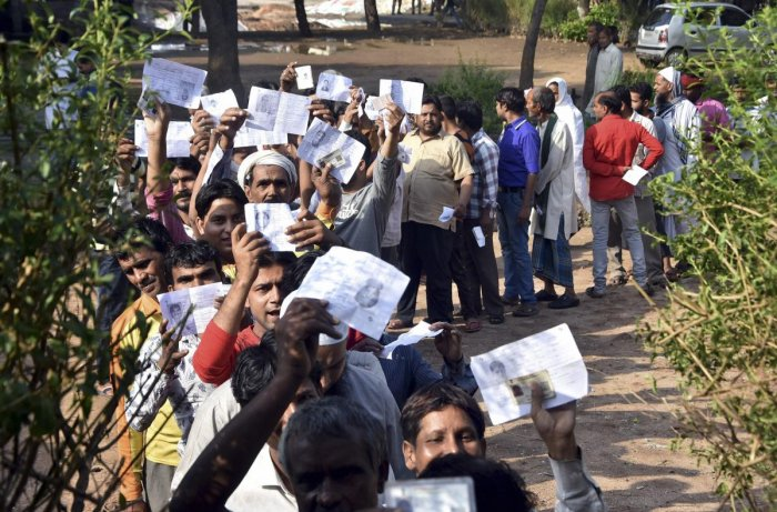 Voters show their identity cards as they stand in a queue at a polling station to cast vote during the second phase of the general elections, in Mathura, Thursday, April 18, 2019. (PTI Photo)