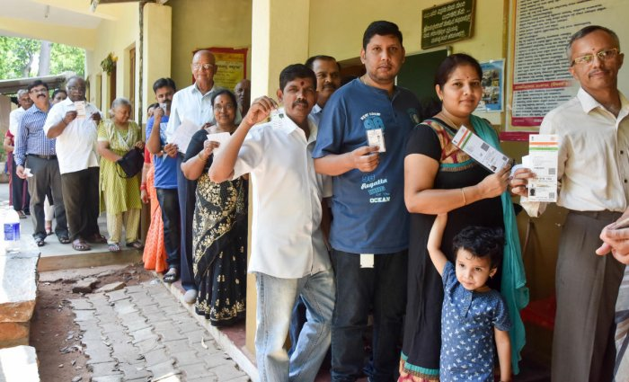 People stand in a queue to cast votes at Kuvempu School, Mysuru.