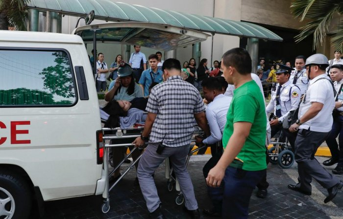 Rescue workers carry a woman to an ambulance after she became dizzy following an earthquake hit Manila, Philippines Monday, April 22, 2019. AP/PTI
