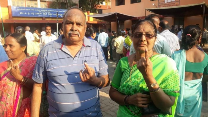 C N Nayak, who lost his mother on Tuesday, along with his wife Indira Nayak, shows the indelible ink mark outside the Bhavani Nagar polling station in Hubballi. DH Photo
