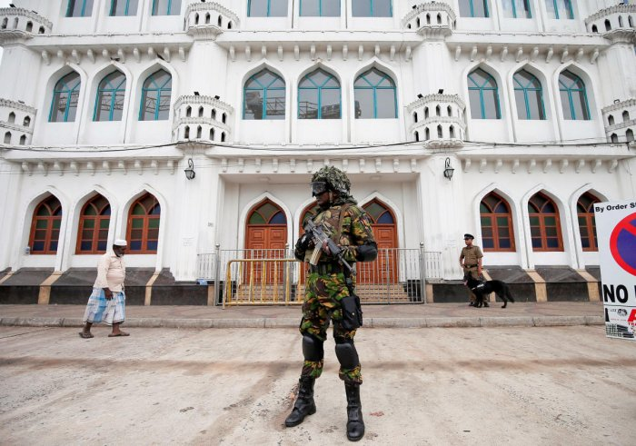 Sri Lankan Special Task Force soldiers stand guard in front of a mosque as a Muslim man walks past him during the Friday prayers at a mosque, days after a string of suicide bomb attacks on Easter Sunday in Colombo. Reuters photo